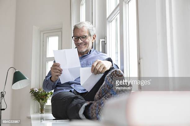 mature man at home sitting at the window reading documents - letter document stock photos and pictures