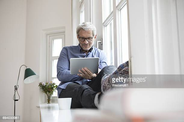 Mature man at home sitting at the window using tablet