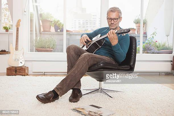 Mature man at home sitting in chair playing guitar