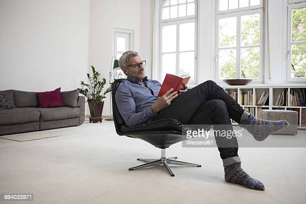 Mature man at home sitting in chair reading book