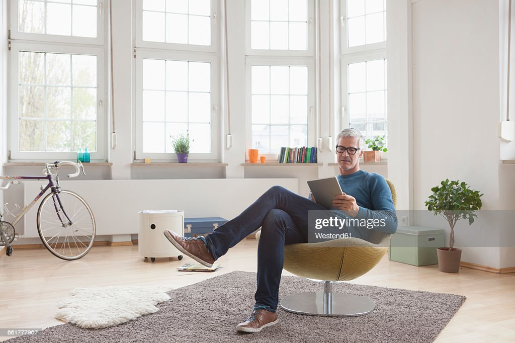 Mature man at home sitting in chair using digital tablet : Stock Photo