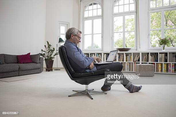 Mature man at home sitting in chair using laptop