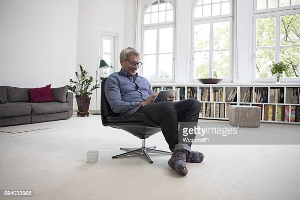 Mature man at home sitting in chair using tablet