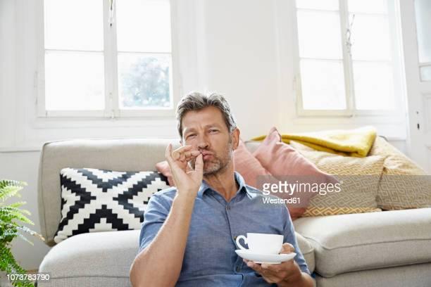 mature man at home sitting in front of couch, drinking coffee - speisen und getränke stock-fotos und bilder