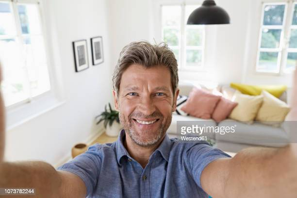 mature man at home taking a selfie - selfie stock pictures, royalty-free photos & images
