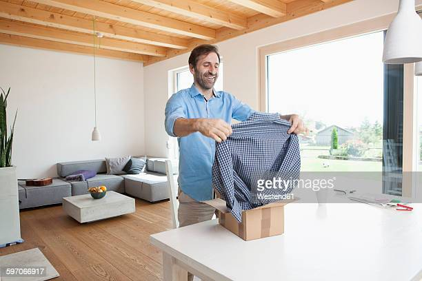 Mature man at home unpacking new shirt