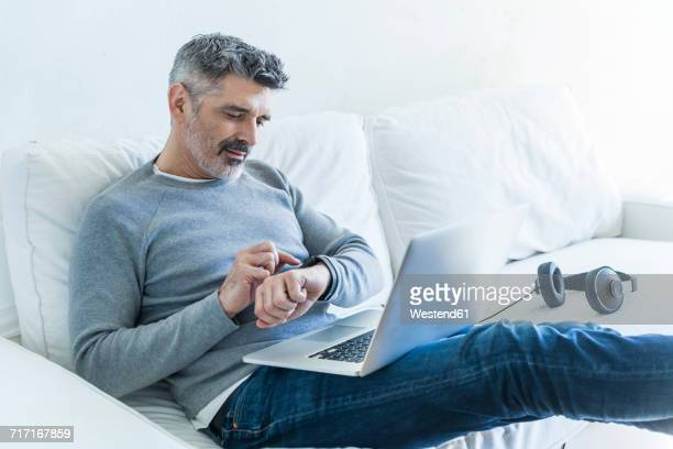 Mature man at home using laptop and checking the time