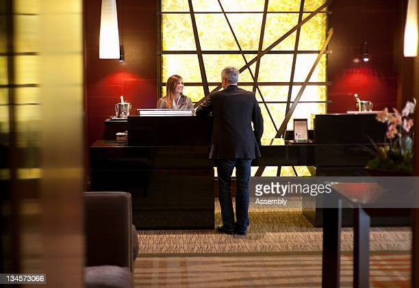Mature man at reception desk in hotel lobby.