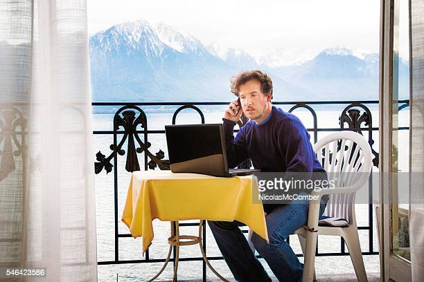 Mature man at work while on holidays in Swizerland