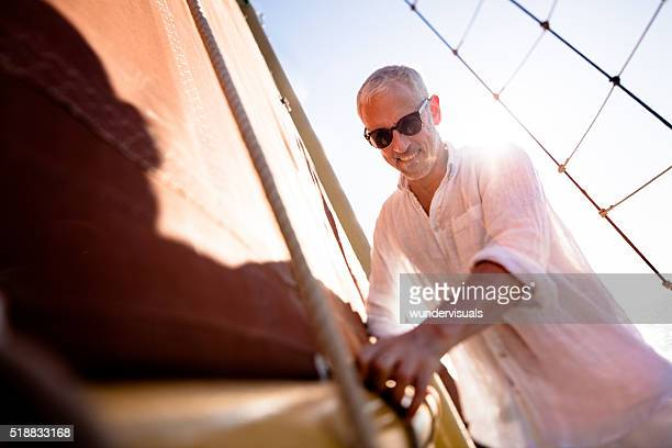 Homme d'âge mûr assister à la principal sur son Yacht voile