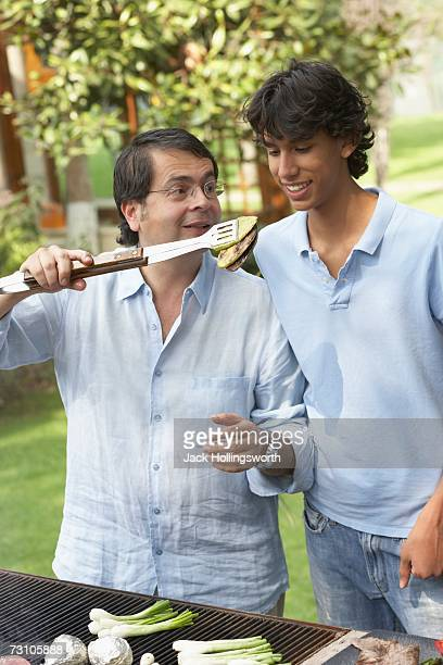 Mature man barbequing with his teenage son