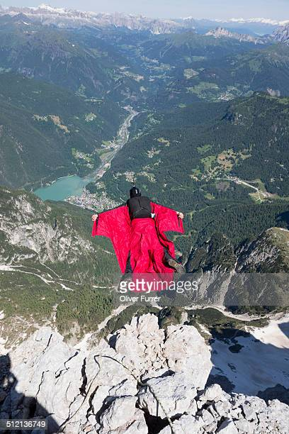 Mature man BASE jumping from mountain, Alleghe, Dolomites, Italy
