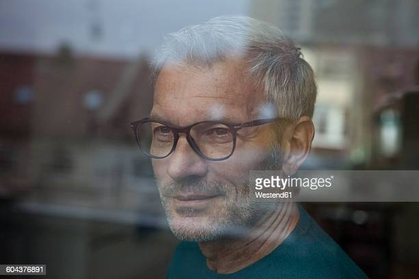Mature man behind windowpane looking out