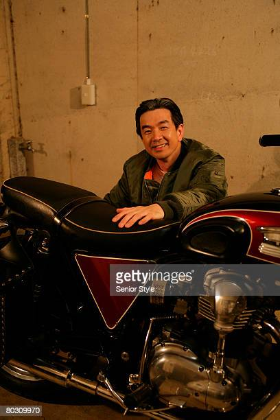 Mature man beside motorcycle, smiling