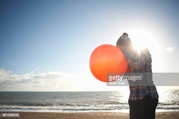 Mature man blowing up inflatable hopper at beach