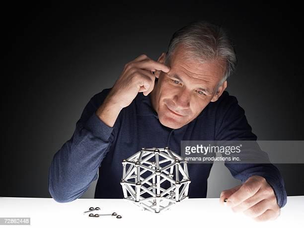 Mature man building polyhedron