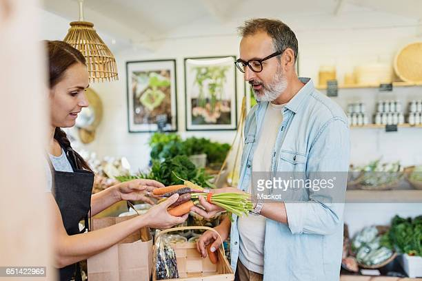 Mature man buying carrots from female clerk at food store