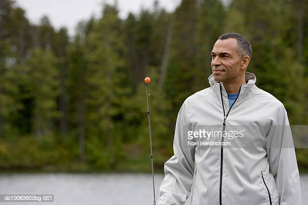 Mature man by lake, holding fishing rod