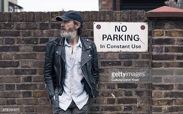 Mature man by no parking sign on brick wall