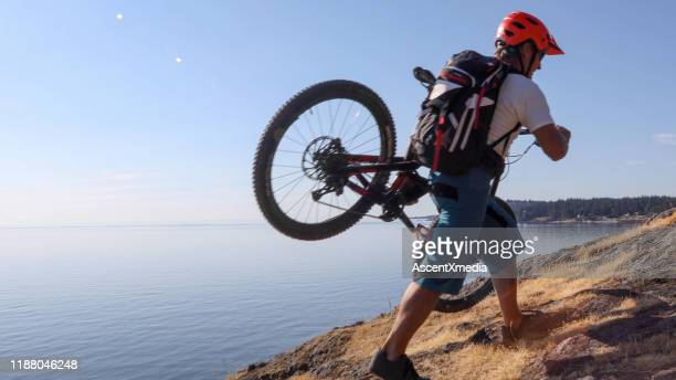mature man carries mountain bike up mountain ridge at sunrise - ascent xmedia stock pictures, royalty-free photos & images