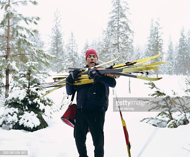 mature man carrying armload of cross-country skis, winter - struggle stock pictures, royalty-free photos & images