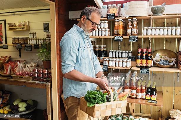 Mature man carrying basket while shopping in food store