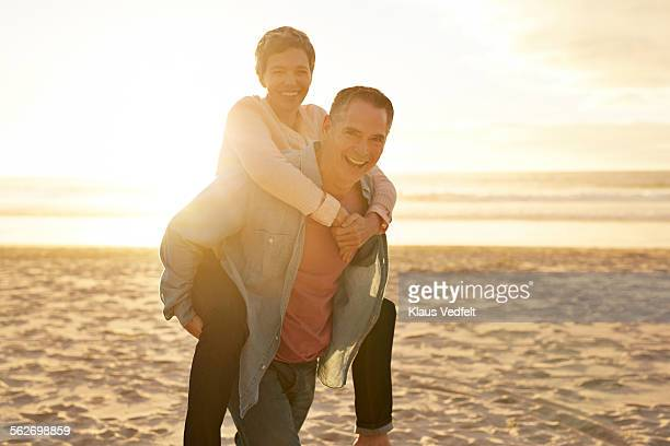 Mature man carrying girlfriend on the back