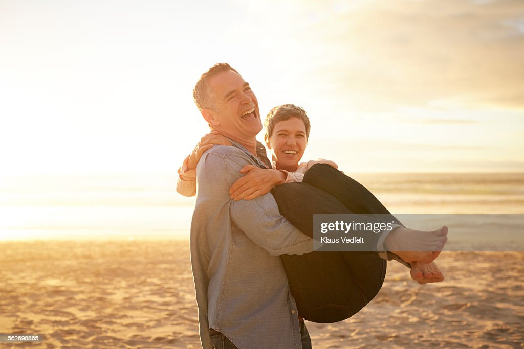 Mature man carrying girlfriend on the beach : Stock Photo