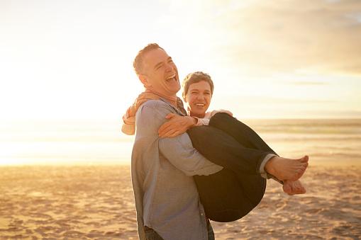 Mature man carrying girlfriend on the beach - gettyimageskorea