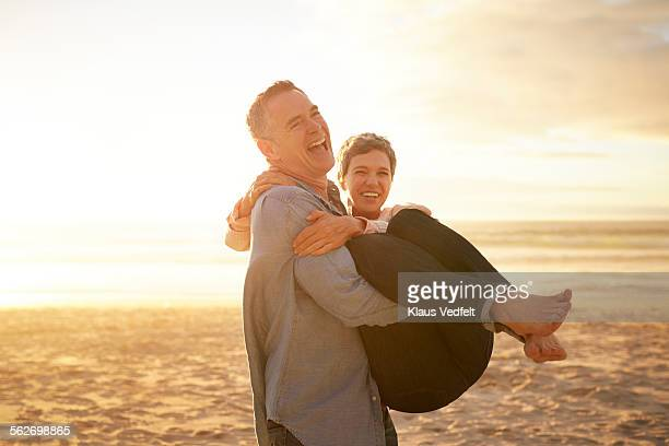 Mature man carrying girlfriend on the beach