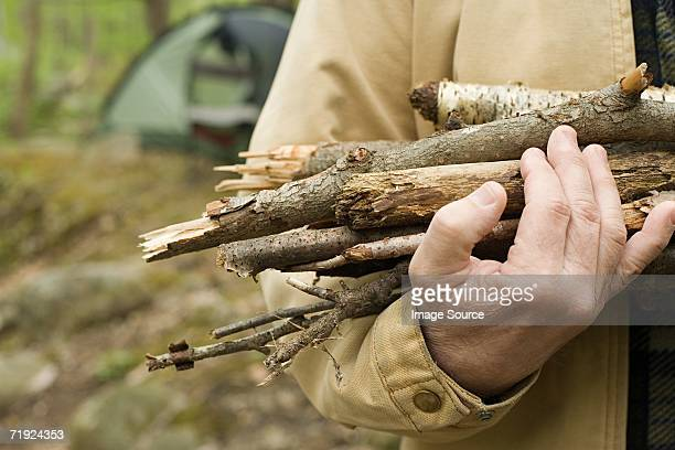Mature man carrying logs