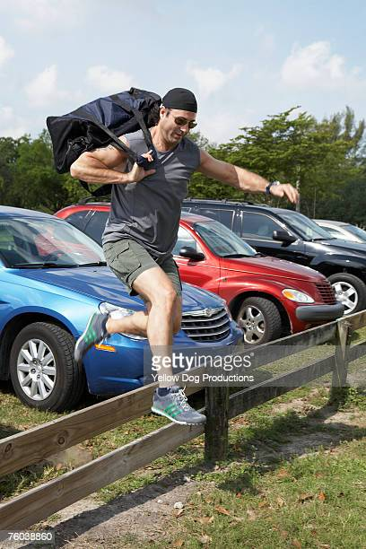 Mature man carrying sports bag jumping over fence