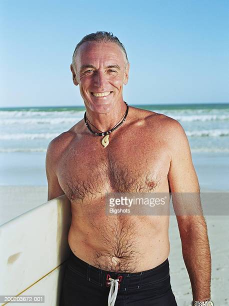 mature man carrying surfboard under arm, smiling, close-up, portrait - hairy chest stock photos and pictures