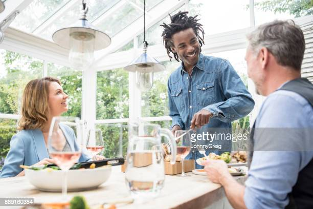 Mature man carving meat at dinner table with two friends smiling and watching