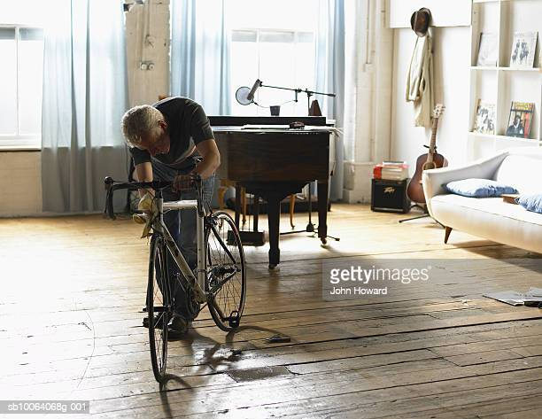 Mature man checking bicycle indoors