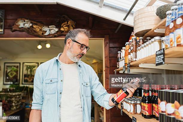 Mature man checking bottle while shopping in store
