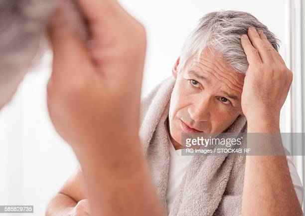 Mature man checking his gray hair in mirror