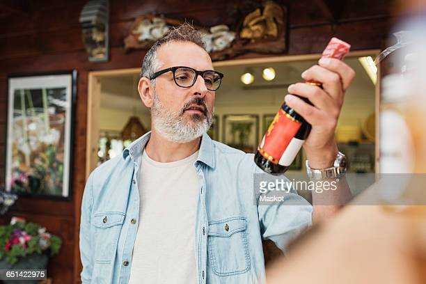 Mature man checking information on bottle while shopping at store