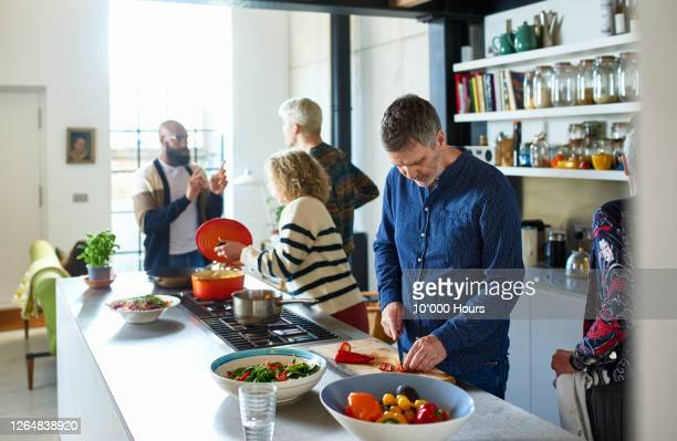 mature man chopping vegetables at home with family - social gathering stock pictures, royalty-free photos & images