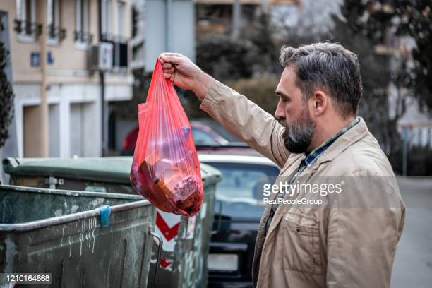 mature man citizen throwing garbage in trash can, preventing littering, environment - human body part stock pictures, royalty-free photos & images