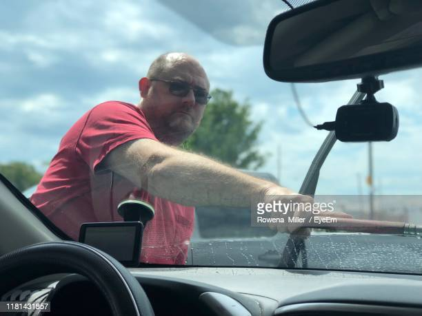 mature man cleaning car windshield - rowena miller stock photos and pictures