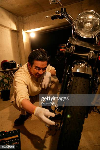 Mature man cleaning his motorcycle
