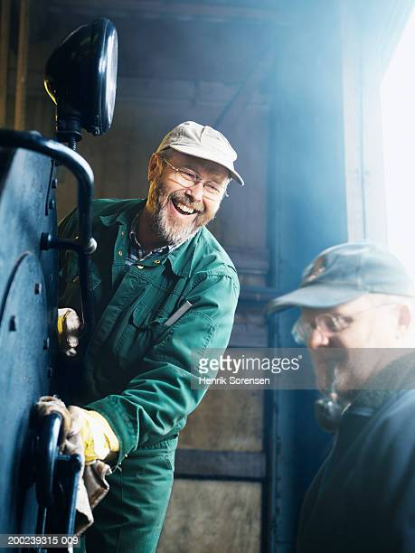 Mature man cleaning machinery, watched by mature man smoking pipe