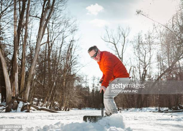 mature man clearing snow - snow shovel stock pictures, royalty-free photos & images