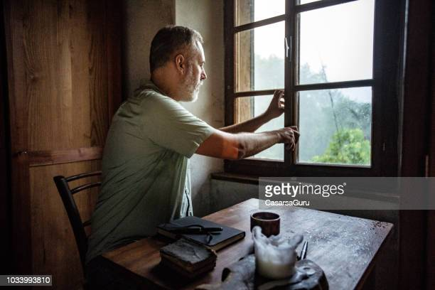 mature man closing a window on a rainy day - closing stock pictures, royalty-free photos & images