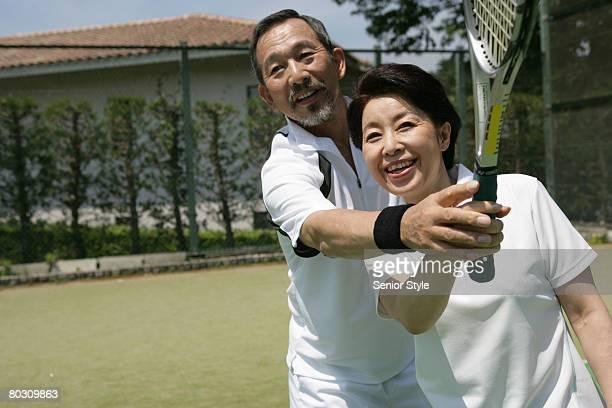 Mature man coaching a woman tennis, close-up