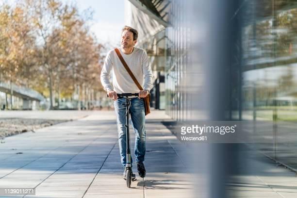 mature man commuting in the city, using kick scooter on the pavement - independência imagens e fotografias de stock