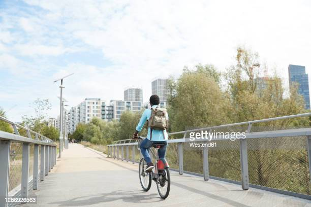 mature man commuting on road with bicycle in city - sustainable lifestyle stock pictures, royalty-free photos & images