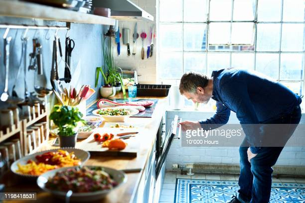 mature man cooking meal and looking in oven - kitchen stock pictures, royalty-free photos & images
