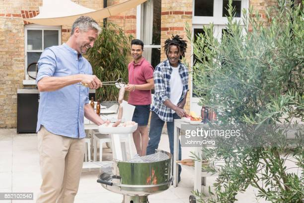 Mature man cooking sausages on barbecue